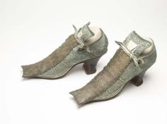 A pair of women's tie shoes, which would have been expensive when they were first made. The uppers are made of white leather and embellished with green silk braid, and a wide gold briad down that centre, now tarsnished, which woud have glittered gold in the light. Their high qulaity and luxurious materials meant they were only worn indoors. 17th century