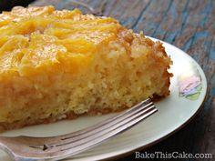 Slice of vintage orange upside down cake with honey orange soak on worn wood by bake this cake