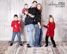 family christmas photo, kids wrap parents in lights