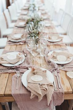 Ethereal Barefoot Wedding in Formentera, Spain. Wooden picnic benches with a rustic tablescape in pink and natural fabrics.