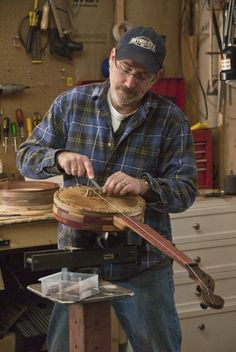 """In his spare time, Jeff Delfield, head librarian at Bryson City, NC Marianna Black Library, builds musical instruments using materials not normally associated with """"fine"""" instrument making — cigar boxes, cookie tins, wooden bowls, flea market finds and antique shop discoveries."""