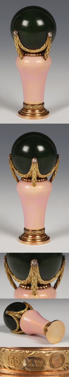 A Faberge carved nephrite, gold and enamel desk seal, workmaster Henrik Wigstrom, St. Petersburg, circa 1908-1917. THe ball shaped nephrite handle mounted with diamond set laurel leaf swags, the baluster shaped collar enamelled with translucent pink over a wavy guilloche ground with a beaded band at the top and a chased laurel leaf band at the bottom