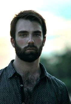 The complete look - his shirt, his hair and his awesome looking full beard.
