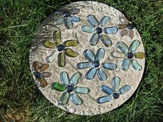 Garden stepping stones. Mix 4 cups of concrete w/ water in a big bowl, pour into  medium plant saucer, smooth out, add flat side of glass stones in any pattern (may engrave it too), let stand 24 hrs, remove plastic & allow to dry another 24 hrs, spray w/ water to clean beads and set stone.