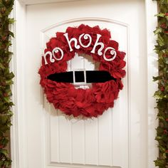 """Have some fun with your Christmas decor this year! The Red Jute Santa Belt Wreath will put a smile on your guests' faces as they see your front door. It features a red ruffled jute with a black and silver Santa belt and the words """"Ho Ho Ho."""""""