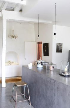 Cement counter tops, old world chandelier and wall inset with copious amounts of candles, hide on the floor, eclectic decor, industrial loft style ceilings... This is insane. I could work with this.