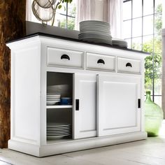 Made of sturdy mahogany wood, this buffet piece has a stunning white finish that will enhance any home decor. Drawers and sliding doors give room for concealed storage, and contrasting hardware and a countertop give a striking look.