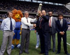27 August 1984: CHELSEA FC Manager JOHN NEAL (in white shirt) is presented with the 1983-84 Canon League Division Two trophy at the first game of the following season, Chelsea vs Sunderland, accompanied by Assistant Manager IAN McNEILL (first left), and CHELSEA player MICKEY THOMAS (first right)...
