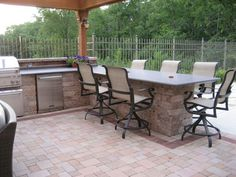 Outdoor kitchen, Pergola & Paver Patio: The granite bar with six bar stools and the built-in refrigerator.