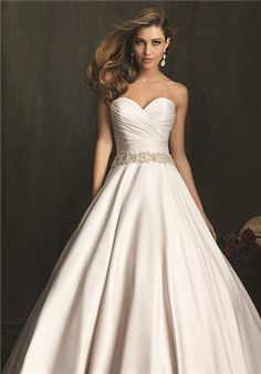 An exquisite ball gown in rich, soft satin.  The strapless bodice features a sweetheart neckline, delicate ruching, and Swarovski crystals at the waistline.  The ball gown skirt is gathered and is finished with a chapel length train
