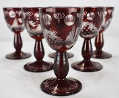 Six Vintage Bohemian Ruby Red Cut to Clear Etched Glass Egermann Liquer Glasses Tapered bowl cranberry red washed to clear.Pattern depicts a swallow, tower and net pattern. Six clear round lenses.Thick, baluster tapered stem. High kick round base with pattern cut to clear through cranberry red overlay.
