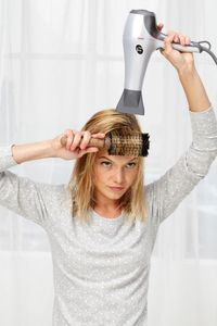 Step 2: If you have bangs, blow-dry them using a big, round brush. Pull them straight out from your forehead and aim the dryer's nozzle toward their ends.