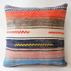 A pillow covered with an antique kilim (a kind of a rug). Its made of cotton. Colored with natural dyes. It has Anatolian and Middle Eastern patterns.