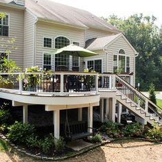 An elevated deck with curved design uses dark and light coloring, post sleeves (covers), under deck landscaping and single stringer stairs for backyard access.