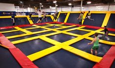Kids and adults bounce around an indoor trampoline park, dunking on basketball hoops, flipping into foam pits, or jumping off walls