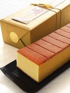 "Castella is a popular Japanese sponge cake type wagashi made of sugar, flour, eggs, & starch syrup. Now a specialty of Nagasaki, the cake was brought by way of Portuguese merchants in the 16th century. The name is derived from Portuguese Pao de Castela, meaning ""bread from Castile"". Castella cake is usually sold in long boxes. This castella is from the famous sweets shop Ginza Bunmeido located in Ginza, Tokyo."