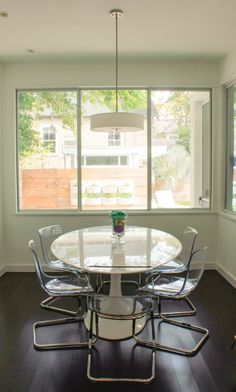 An oval fiberglass dining table paired with acrylic chairs