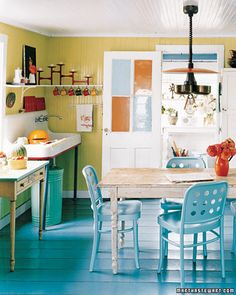 Sweet little beach cottage kitchen! As are the red muffin tins propped above the faucet and the red racing stripe Elena applied to the base of her vintage sink. The ribbon detail hides pesky rust spots and the tins provide a pop of color.    Again - love the colors aqua, yellow and orange