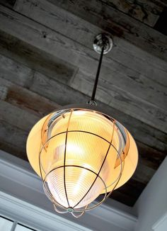 A fixture provided by Circa Lighting hangs from a wood ceiling at the 2013 Coastal Living Showhouse on Daniel Island.