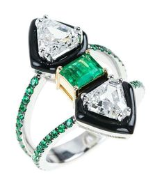 Nikos Koulis creates this unique engagement ring using black enamel. This diamond engagement ring is set with a central emerald and additional pavé emeralds around the double band.