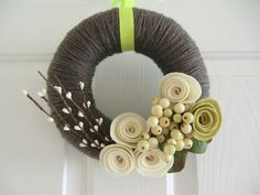 yarn wrapped wreath-need to figure out how to make those flowers.