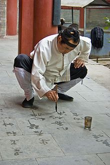 A Taoist monk practicing Chinese calligraphy with water on stone. Water calligraphy, like sand mandalas, evokes the ephemeral nature of physical reality.