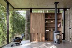 The living roomis anchored in the forest but features an expansive water view.The ceilings are clad in finished plywood panels, and the home is filled with built-ins for storage and aMorso woodstove.