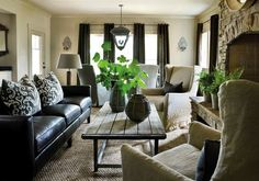 How to make leather couches cozy: team with distressed wood, linen covered wingback chairs, sizal rug and a touch of greenery to freshen it up.