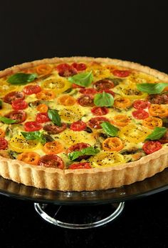 Photo of a Tomato Basil Fresh Mozzarella Tart on a glass cake stand with a back background.