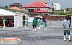 News Photo : Health workers walk inside the Nongo ebola...