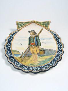 QUIMPER POTTERY SHELL-SHAPED SERVING PLATTER, hand painted under glaze with barefoot fisherman holding net and basket, having cobalt blue prunus border. Signed HR Quimper front and verso. c. 1904-1922.