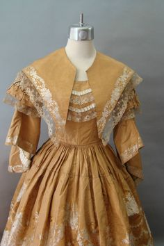 1850s dress with two flounces hand stitched to the silk underskirt. The type of fabric used is woven a la disposition. This dress has detachable pagoda sleeves and pelerine. Without them the dress is a ballgown; with them it is appropriate for day, with a chemisette and undersleves.  The bodice has applied trim of pleated silk ribbon and lace. The pagoda sleeves were basted on. The skirt is cartridge pleated all the way around. The bodice is lined with polished cotton. Click to see other…