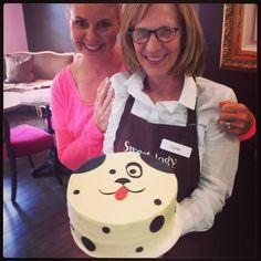Kara and Linda striking a pose with an adorable puppy cake made at Sweetology!