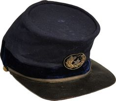 "General's Chasseur Style Cap with Brigadier General's Cap Insignia. Original gold bullion embroidered wreath with silver bullion star on a blue velvet background sewn on the front. The fine blue wool body rises to 3 7/8"" at the front, the band constructed of deep blue velvet reflective of the velvet collar and cuffs seen on General's frock coats. In lieu of a chinstrap the piece exhibits a 1/4"" wide toned gold band held fast with staff eagle buttons - one detached."