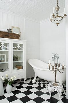 Black and white checkered bathroom tiles make this room amazing. The best part of the design? The smaller tiles beneath the tub. It draws the eye to the bath and makes it the focal point of the room. Click through to see more black and white interior design.