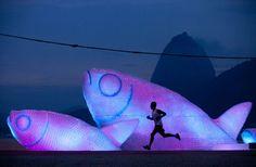 A man runs on Botafogo beach near a brightly-lit sculpture made from plastic bottles. (AP Photo/Felipe Dana)