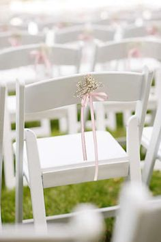 Delicate Baby S Breath Ceremony Decor Tied To White Folding Chairs With A Pink Ribbon