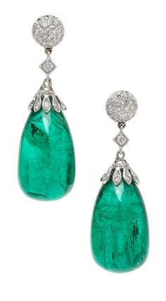 A pair of white gold, diamond, and emerald earrings. Those emerald drops weigh 28 carats!