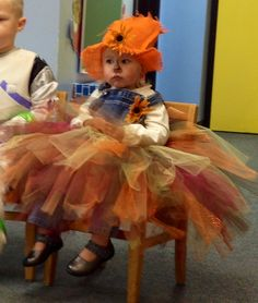 Girl scarecrow costume made with fall colored tulle attached to overalls and a burlap hat