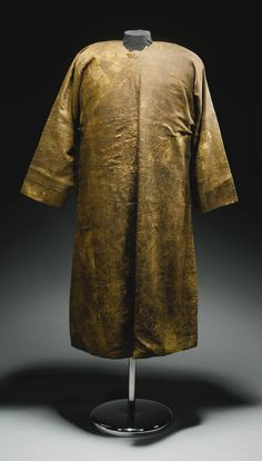 A rare silk lampas robe, Sogdiana, Central Asia, 7th/8th century. robe of characteristic form with long sleeves and open front fastened on the side. Of fine honey colored and dark brown silk threads, decorated with large medallions containing two confronted dragons, between scrolling leafy vines issuing palmettes, mounted on a later silk lining. 113cm. height.