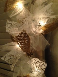 Beautiful handmade garland created with burlap, ivory tulle, lace, and 50 count light string. This 12 foot long garland would look great across a