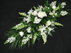 An elegant white casket spray including lilies, freesia and roses, with palm leaves. Casket Flowers, Grave Flowers, Church Flowers, Funeral Flowers, Diy Flower Arrangements For Funeral, White Flower Arrangements, Funeral Caskets, Funeral Sprays, Freesia Flowers