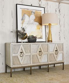 Diamond Multi Use Cabinet As versatile as it is beautiful, this design functions as a media cabinet, console, or sideboard. Made from solid Gmelina Wood and finished in iridescent driftwood, the cabinet sits atop an iron base with a gold finish. Drop handles are made of solid brass. Each of the three drawers has one adjustable shelf and one grommet to allow easy access for wiring electronic components. Ambella Home #HPmkt 310 N. Hamilton #110