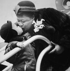 American jazz singer Ella Fitzgerald leans over to kiss an unidentified young boy as she stands on the steps of an airplane. She wears a fur coat, an orchid and a hat with a veil. 1955