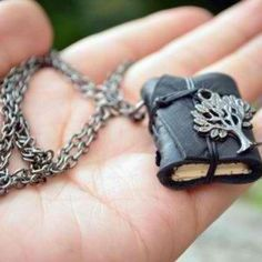 Book necklace, made from leather, paper and metal.