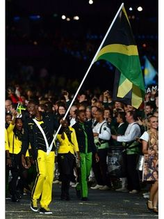 Usain Bolt carries the Jamaican flag during the Opening Ceremony