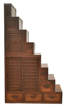 A JAPANESE LACQUERED PINE STEP CABINET the kaidan-tansu with multiple tiers housing cupboards and drawers, iron handles, 136 x 232 x 64cm