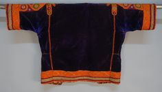 EMBROIDERED BEDOUIN LADY'S VELVET JACKET, 20th C. Purple velvet with short sleeve heavily decorated in couched orange, cranberry, olive and metallic gold threads