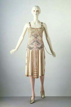 Evening dress, Jean Patou, 1925-26. This sleeveless dress has a low square neckline, which was popular in the mid 1920s. Its straight bodice is embroidered with a design that reveals the influence of Egyptian patterns.