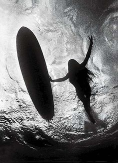 surf girl and her surfboard silhouettes seen underwater